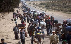 FOR USE AS DESIRED, YEAR END PHOTOS - FILE -In this March 4, 2011 file photo, men from Bangladesh, who used to work in Libya but recently fled the unrest, walk with their belongings alongside a road, as they head to a refugee camp after crossing the Tunisia-Libyan border, in Ras Ajdir, Tunisia. (AP Photo/Emilio Morenatti, File)